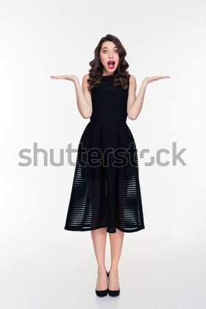 Beautiful wondered retro styled girl holding copyspace on both palms  Stock photo © deandrobot