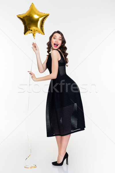 Cheerful excited female with retro hairstyle holding star shaped balloon Stock photo © deandrobot