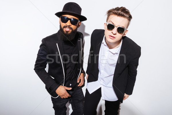 Two serious young men standing and staring on you  Stock photo © deandrobot