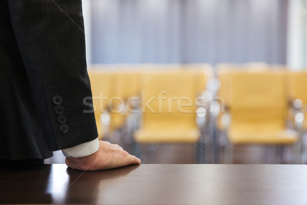 Businessman standing in empty meeting hall Stock photo © deandrobot