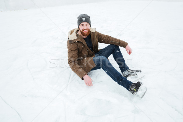 Man sitting on the snow in ice skates  Stock photo © deandrobot
