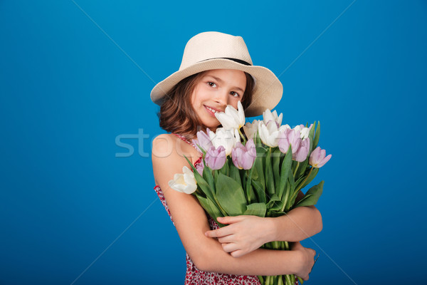 Smiling beautiful little girl in hat holding bouquet of tulips  Stock photo © deandrobot