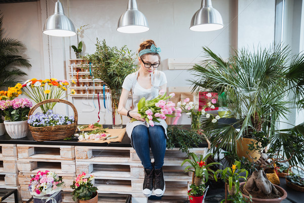 Woman florist sitting and arranging pink tulips in flower shop Stock photo © deandrobot