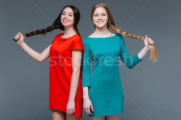 Two smiling beautiful women standing and showing their long braids  Stock photo © deandrobot