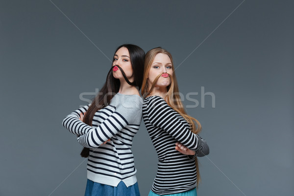 Two funny young women making moustache with their hair  Stock photo © deandrobot