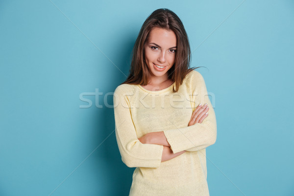 Stock photo: Smart beautiful girl standing arms crossed over blue background