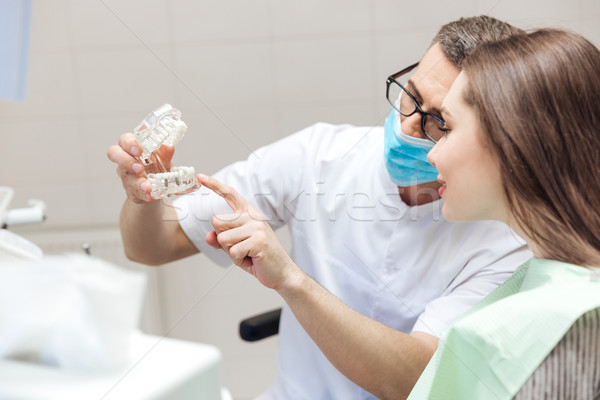 Man dentist show dentures teeth at dental surgery to patient Stock photo © deandrobot