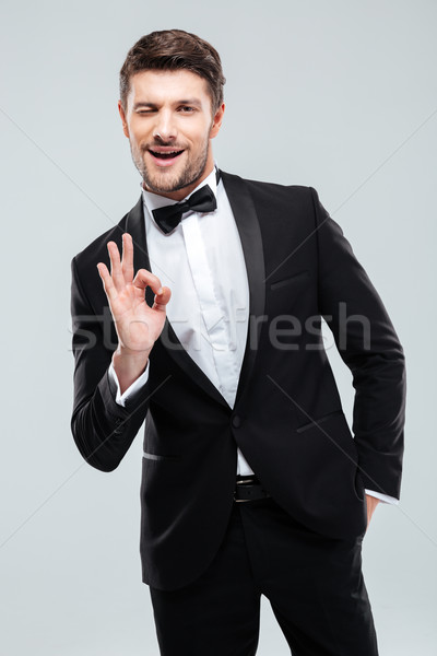 Smiling young man in tuxedo with bowtie showing ok sign Stock photo © deandrobot