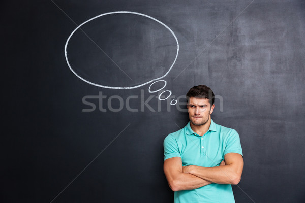 Sad frowning young man standing over chalkboard background Stock photo © deandrobot