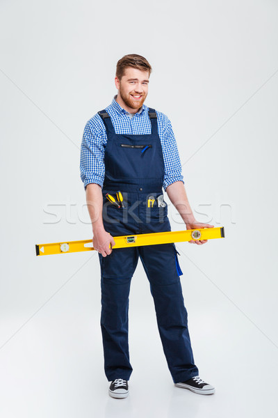 Smiling male builder holding waterpas Stock photo © deandrobot