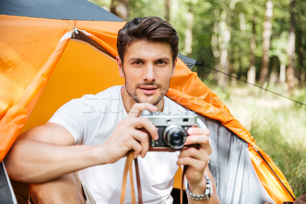 Handsome man with vintage photo camera sitting in touristic tent Stock photo © deandrobot
