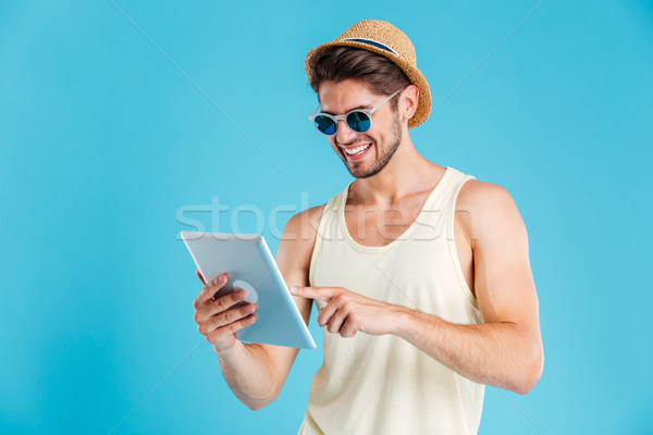 Cheerful young man in hat and sunglasses using tablet Stock photo © deandrobot