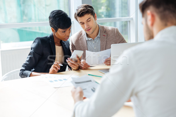 Businesspeople having meeting at the table in modern office Stock photo © deandrobot