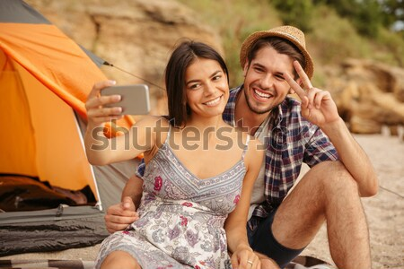 Stock photo: Young happy couple playing guitar while sitting at the beach