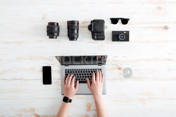 Hands of young man using laptop on wooden table Stock photo © deandrobot