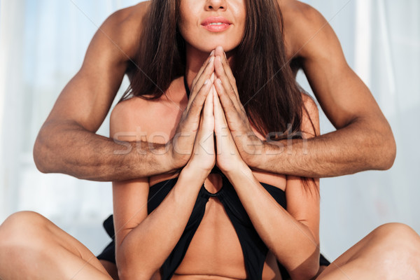 Cropped position of a multiracial couple mediating at the beach Stock photo © deandrobot
