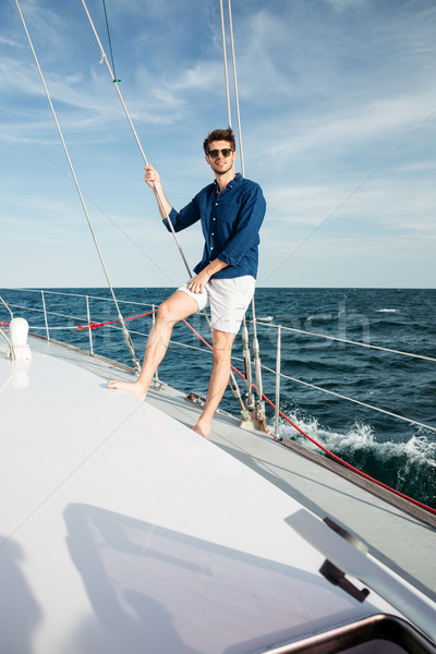Man looking forward and smiling while standing on the yacht Stock photo © deandrobot