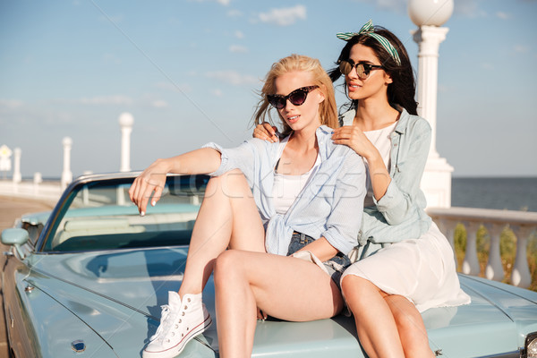 Two women sitting on car tohether in summer Stock photo © deandrobot