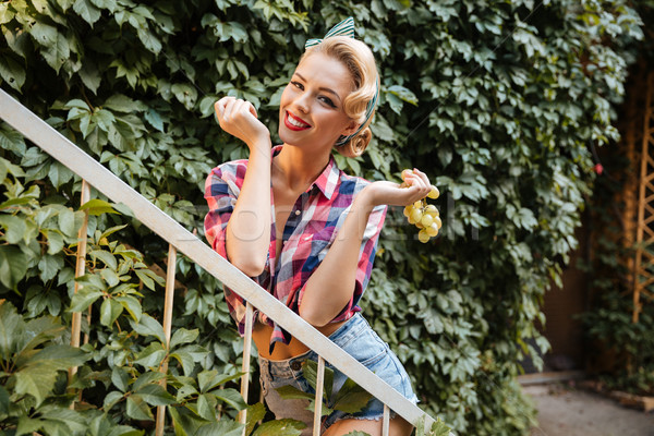 Pin-up girl holding and eating bunch of grape Stock photo © deandrobot