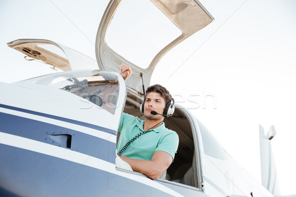 Confident young man pilot in small plane Stock photo © deandrobot