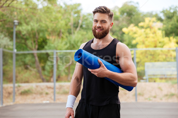 Smiling cheerful fitness man with yoga mat standing outdoors Stock photo © deandrobot