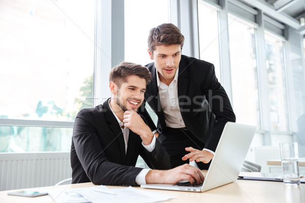 Two cheerful young businessmen using laptop on business meeting together Stock photo © deandrobot