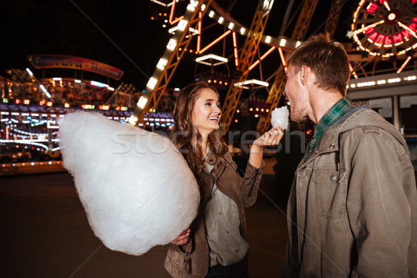 Couple eating cotton candy in amusement park Stock photo © deandrobot