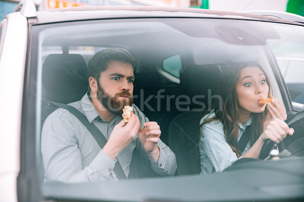 Young couple eating in car Stock photo © deandrobot