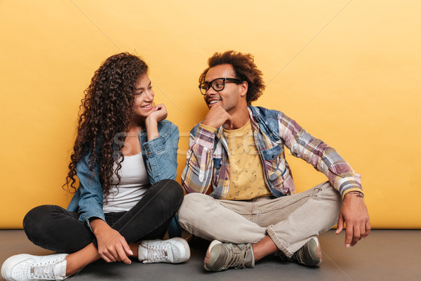 Happy african young couple sitting and looking at each other Stock photo © deandrobot