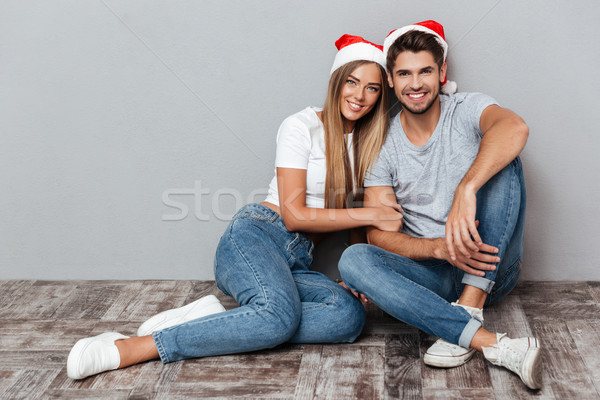 Smiling couple in christmas hats are siting Stock photo © deandrobot