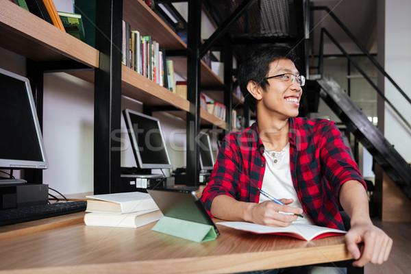 Happy asian male student using tablet at library and writing Stock photo © deandrobot