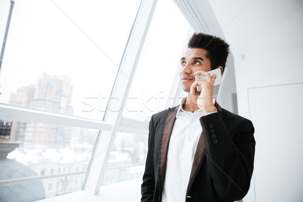 From below image of african business man talking on phone Stock photo © deandrobot