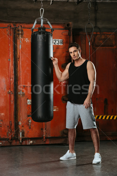 Strong boxer standing in a gym near punch bag Stock photo © deandrobot