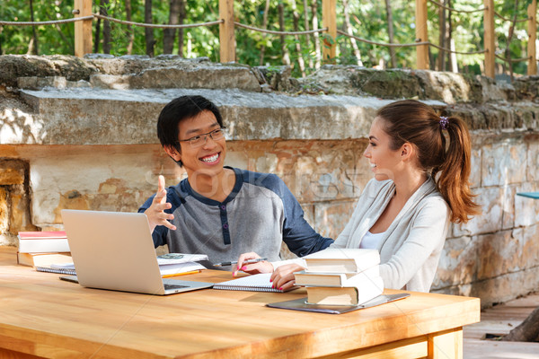 Happy young couple of students studying with laptop in cafe Stock photo © deandrobot