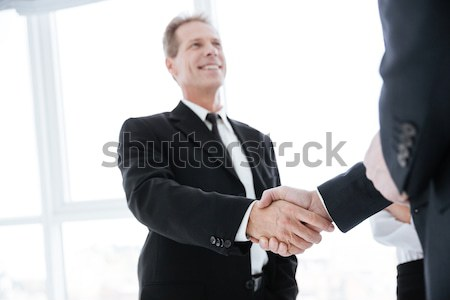 Business people shaking hands near the window Stock photo © deandrobot