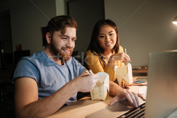 Cheerful business colleagues working at night in office while eating Stock photo © deandrobot