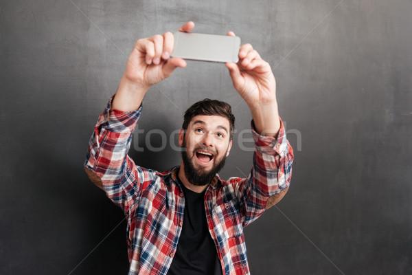 Heureux barbu jeune homme téléphone portable Photo stock © deandrobot