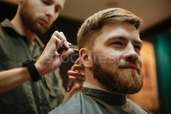 Image of cheerful man getting haircut by hairdresser in barbershop Stock photo © deandrobot