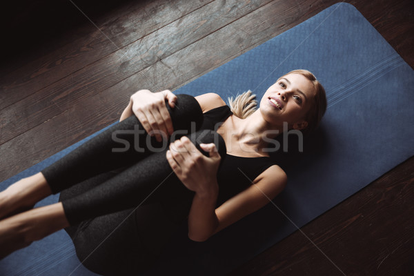 Happy pretty young sportswoman lying and stretching Stock photo © deandrobot