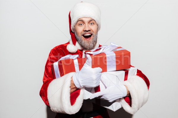 Happy man santa claus holding gifts and showing ok sign Stock photo © deandrobot
