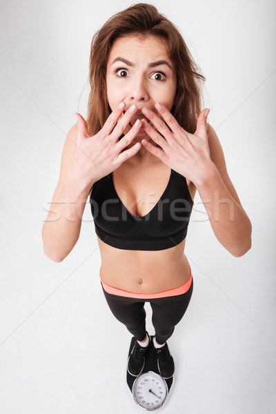 Shocked astonished young fitness woman standing on weighting scale Stock photo © deandrobot