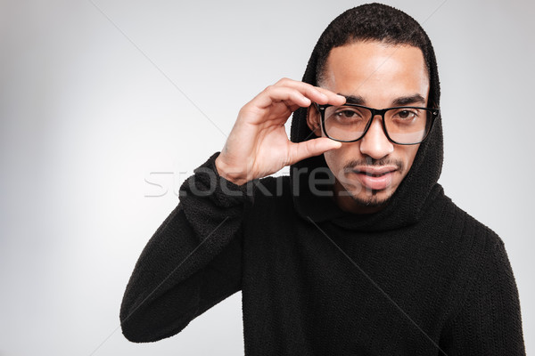 Handsome african american young man in glasses and black hoodie Stock photo © deandrobot