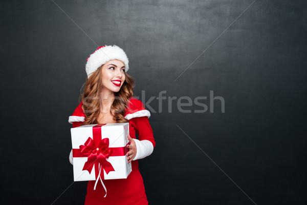 Woman in red santa claus outfit holding big xmas present Stock photo © deandrobot