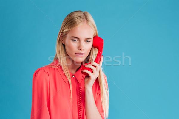 Sad blonde woman holding phone tube Stock photo © deandrobot