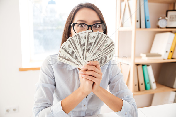 Stock photo: Businesswoman holding money in hand near face
