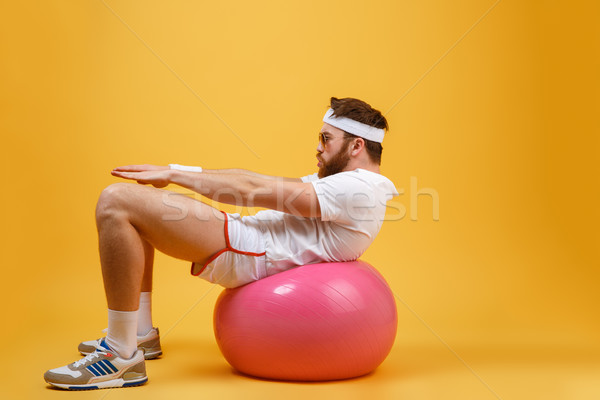 Side view of sportsman Shakes the press on fitness ball Stock photo © deandrobot
