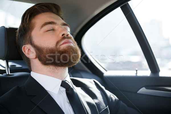 Business man sleeping in the back seat of a car Stock photo © deandrobot