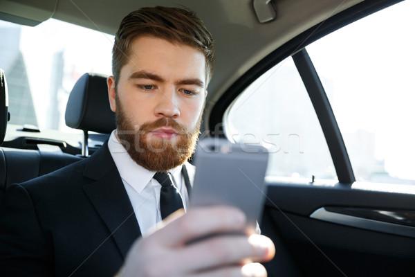 Szakállas üzletember öltöny néz mobiltelefon kéz Stock fotó © deandrobot