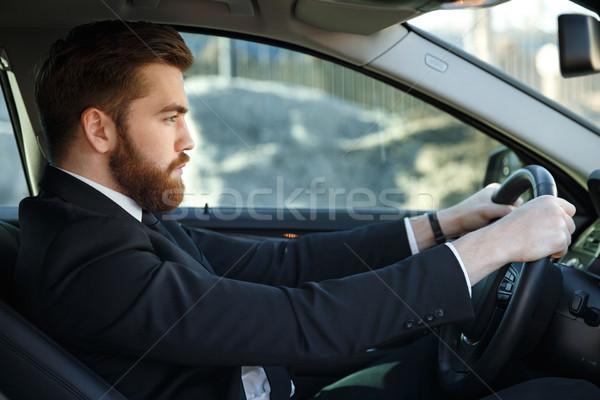 Grave barbado hombre de negocios conducción coche vista lateral Foto stock © deandrobot