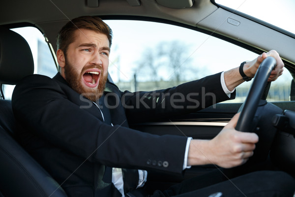 Screaming young business man getting into car accident while driving Stock photo © deandrobot